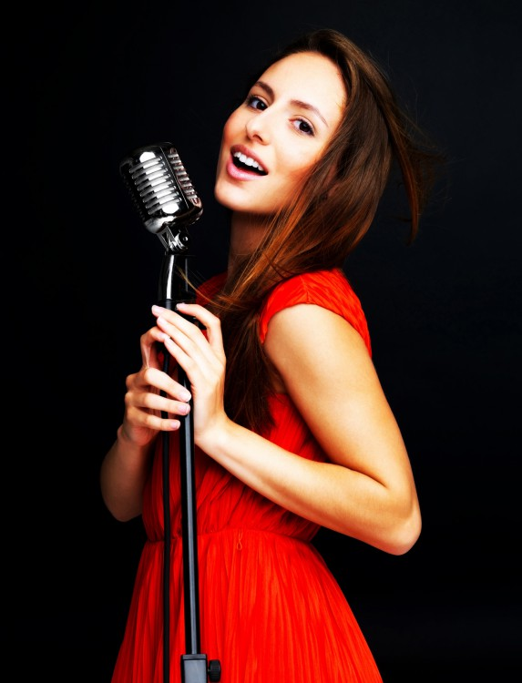 Young female jazz singer singing with old fashioned microphone