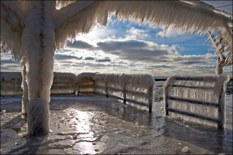 Following a few days of high waves and freezing temperatures, the pier leading to the St. Joseph, Michigan lighthouses is covered in a thick, shining layer of ice.